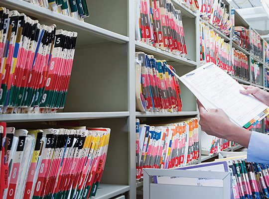 Someone standing in front of library of patient files, looking at a patient's chart