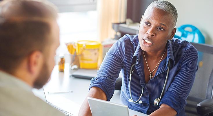 Doctor speaking to her patient from across her desk