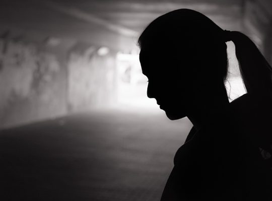 Woman standing in darkness