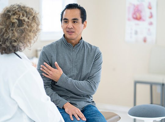 Patient speaking with his doctor in her office
