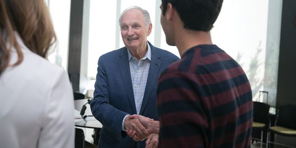 Alan Alda smiling, shaking hands with someone