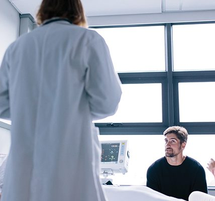 Physician speaking to patient and loved ones at bedside