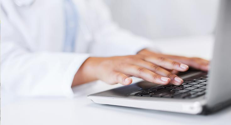 Close-up shot of physician's hands on laptop keyboard
