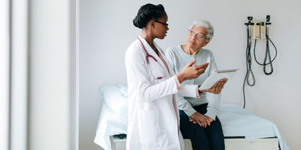 A physician speaks to an elderly patient