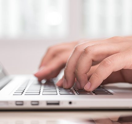 Close-up of hands on a laptop keyboard
