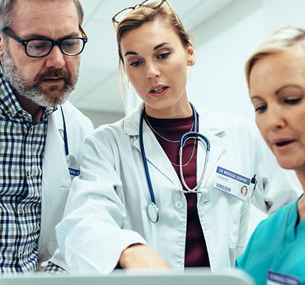 Three doctors conferring over a chart
