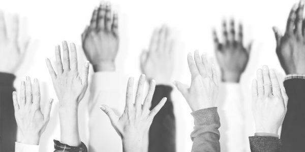 Photo of people's raised hands, as if to volunteer