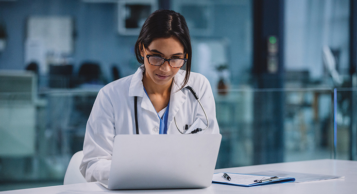 Female physician looking at a laptop