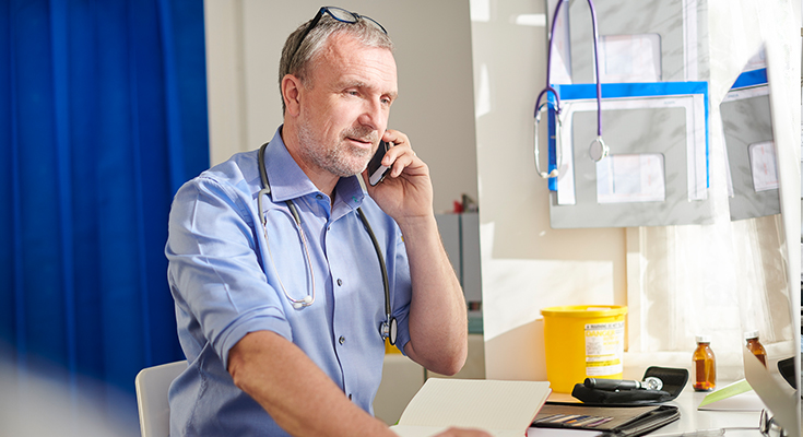 A man speaking on a phone in a medical office
