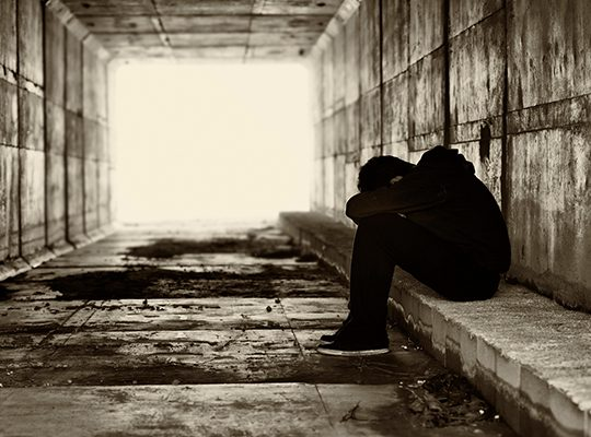 Photo of someone looking dejected in a dark alley