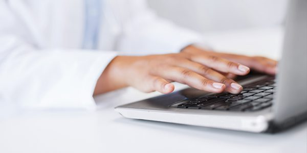 Close-up of physician's hands on a laptop keyboard