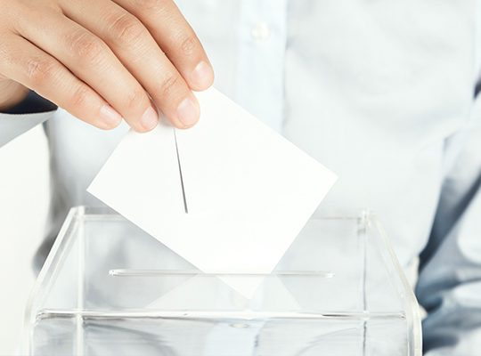 Person dropping a ballot into a box
