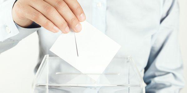 Person dropping a ballot into a box