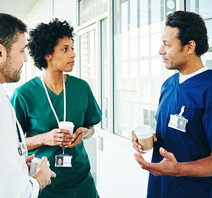 Three healthcare providers conversing in a hallway