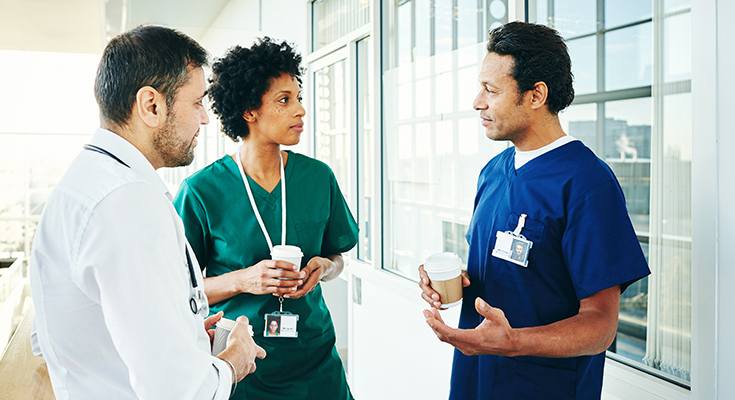Three healthcare providers conversing in a hallway
