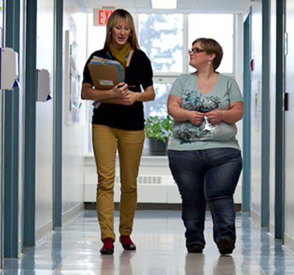 Two women walking down a hallway