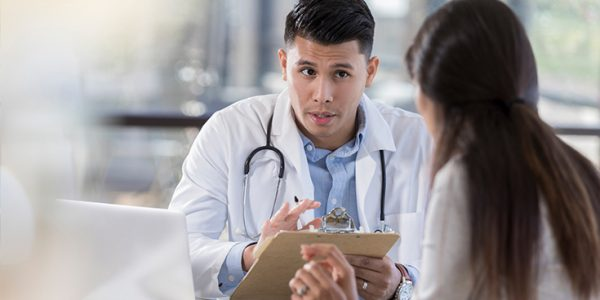 Physician speaking to someone holding a clipboard