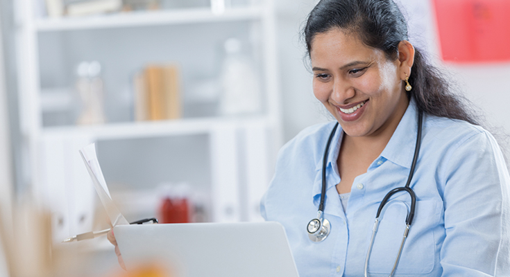 A smiling physician reviewing a chart