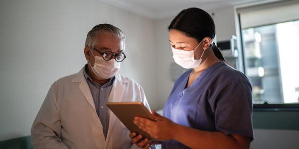 A physician reviews a chart with an assistant