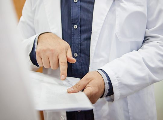 A physician pointing to something on a chart