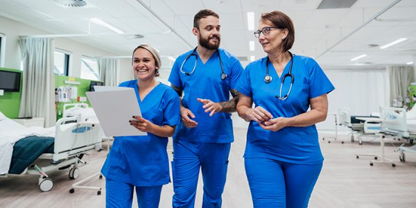 Three healthcare workers walking in a ward
