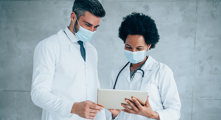 Two physicians discussing a information on a tablet