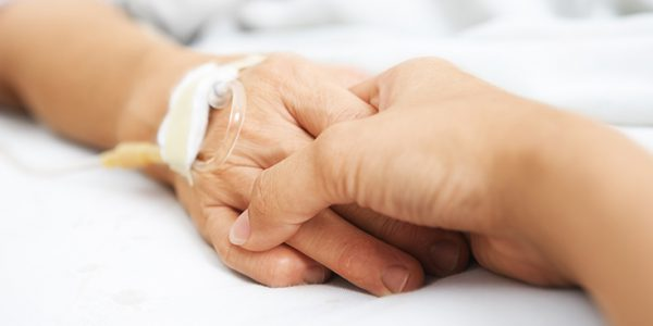Two people holding hands, one has an intravenous line