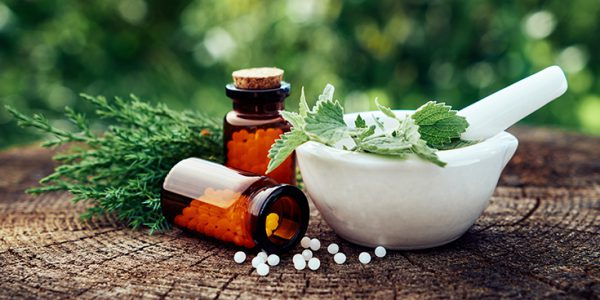Pills next to a mortar bowl filled with herbs