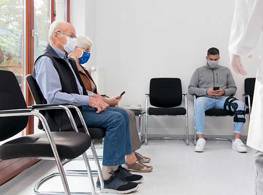 Masked patients sitting in a waiting room