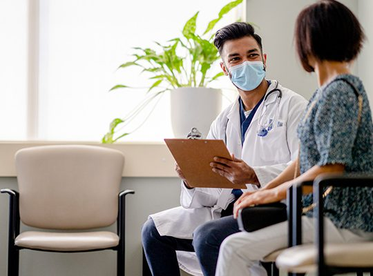 Masked physician speaking to a patient