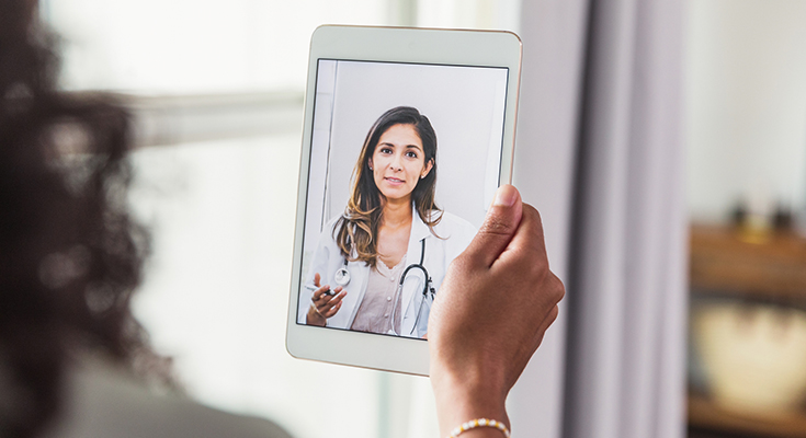 Someone video conferencing with a physician on their tablet